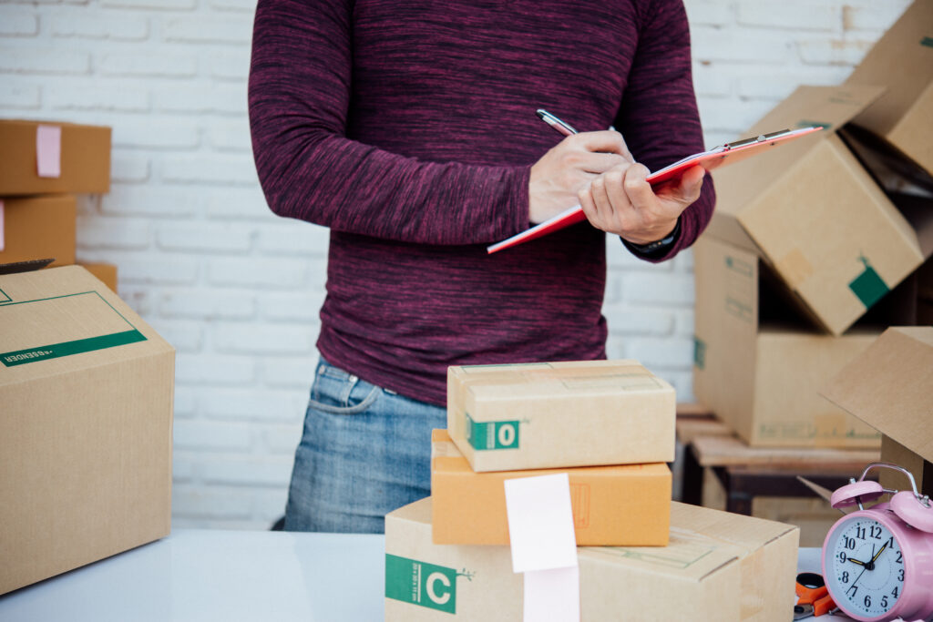 Handsome Young man working with papers among parcels at table in